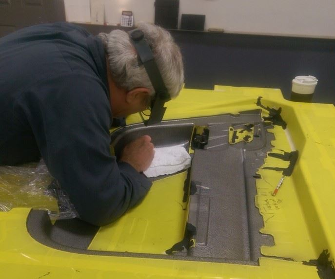 A technician at Custom Etch manually applying a pattern for texturing a mold.