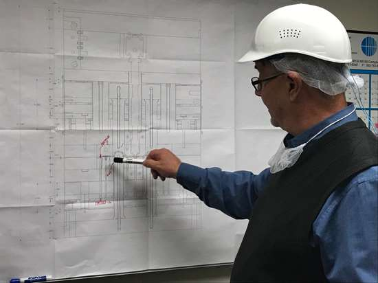 man pointing to schematic
