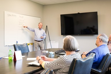 A photo of Mark Beck leading a work flow session between JMC and KAM employees
