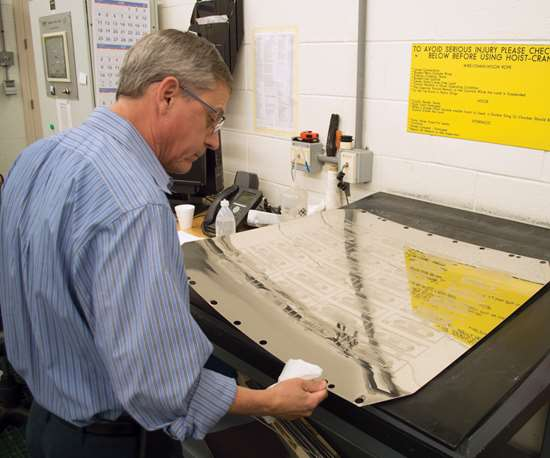 man looking at printing plate