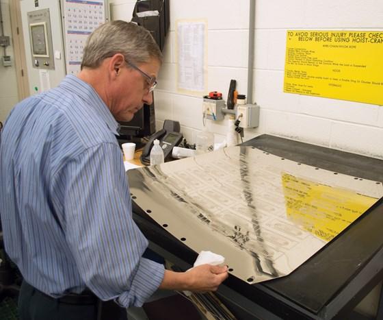 man looking at printing plate