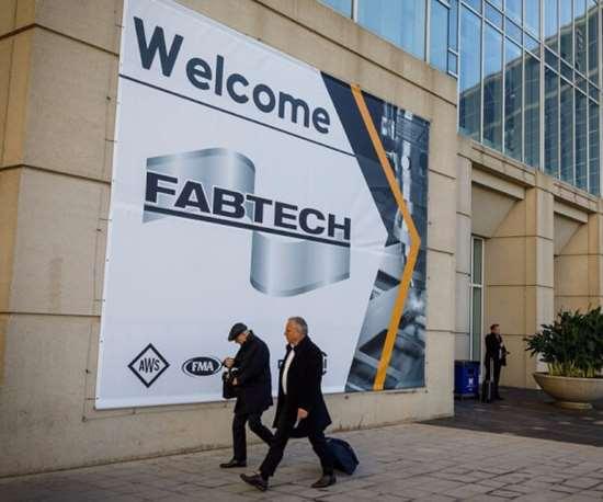 men walking into fabtech show