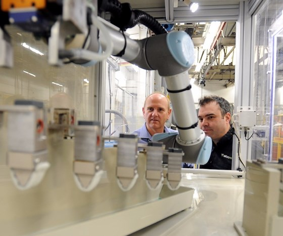 men looking at robot coating parts