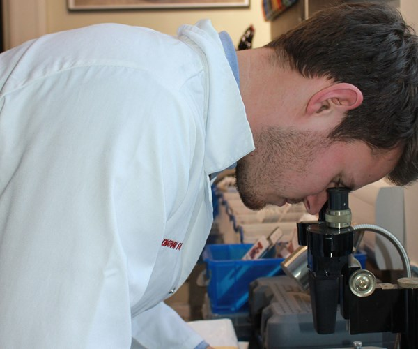 man looking at microscope
