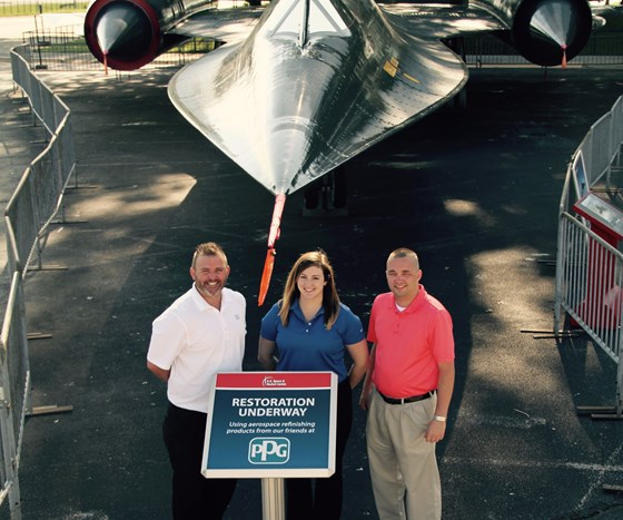 three people standing in front of a plane