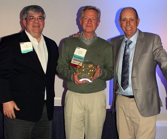 man receiving award from two men