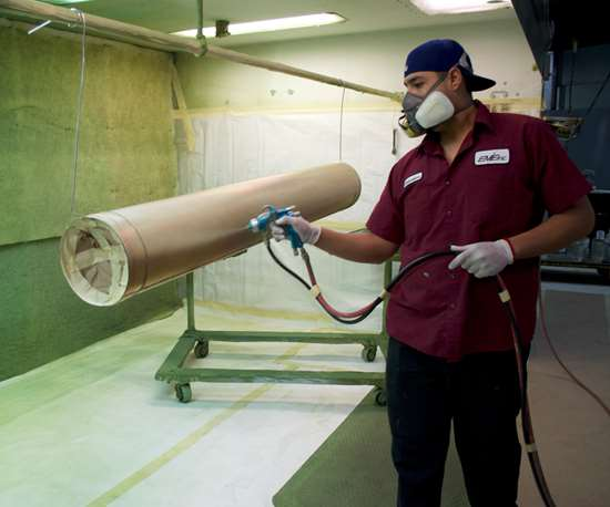 EME employee spraying liquid paint
