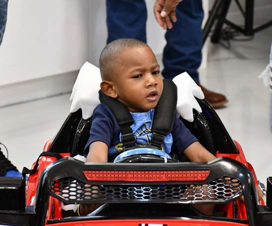 child in a toy car