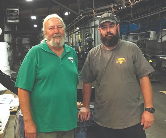 two men standing on shop floor