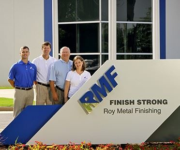 members of the Roy family in front of company sign