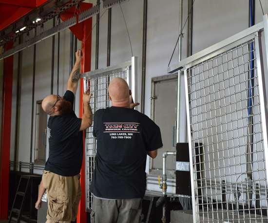 men putting parts on a rack