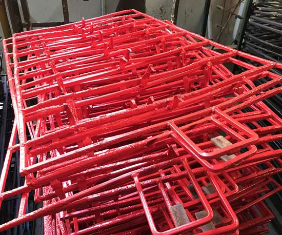 Part racks covered in paint ready for stripping with Atotech's Master Remover 7000