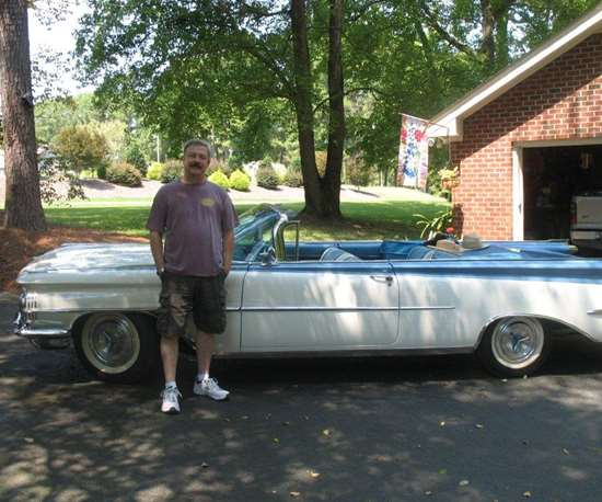man standing in front of older car