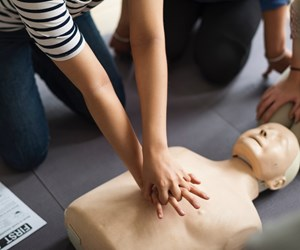 person performing cpr on a practice dummy.