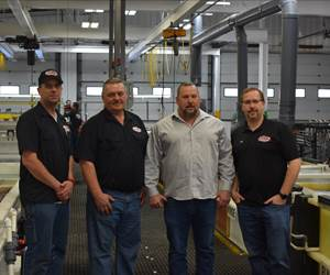 four people standing in a plating facility