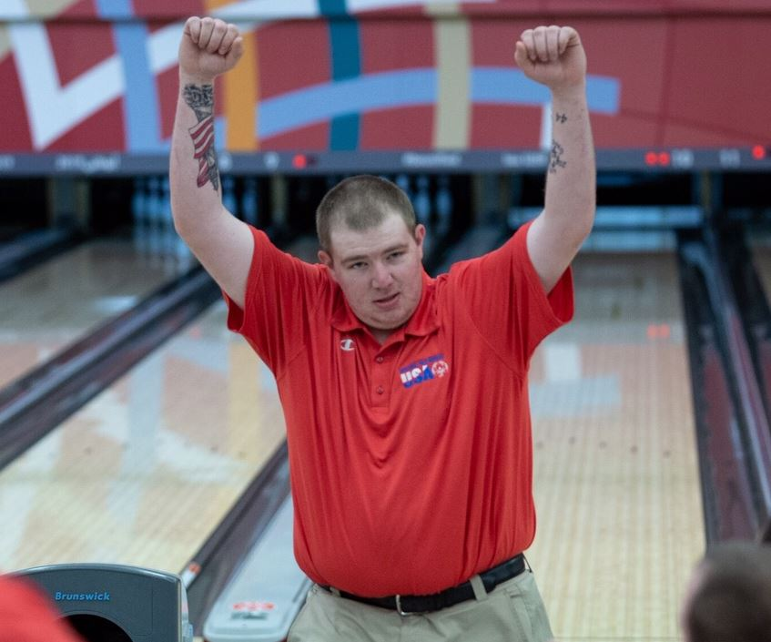Tyler Baxter raising his arms above his head after bowling