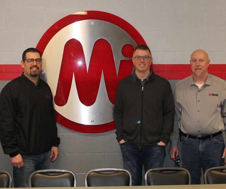 3 men standing near a logo