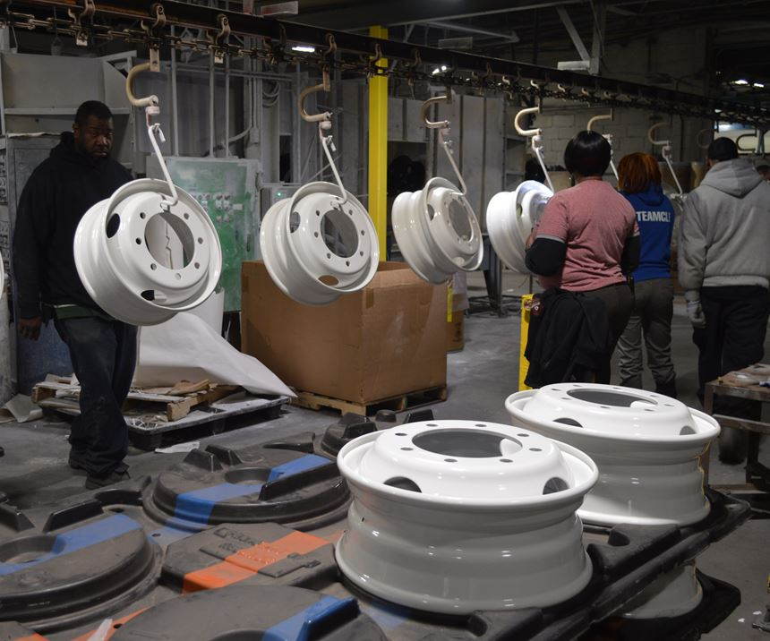 powder coated truck wheels on an assembly line