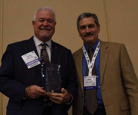 two men standing holding award