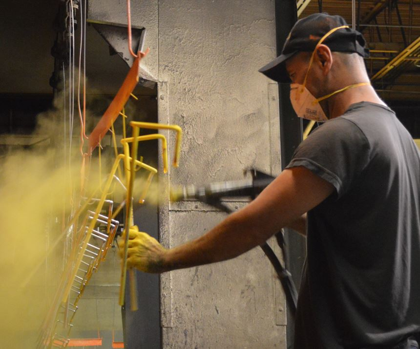 man spraying powder coating