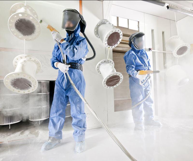 men spraying powder