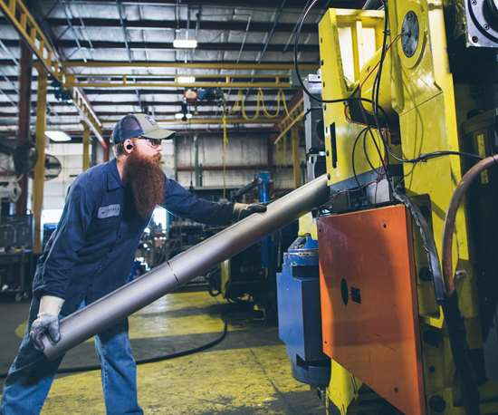 man bending tubes with a machine