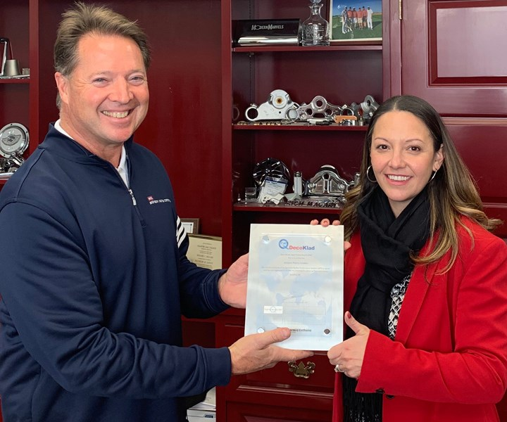 Richard Macary, president of Arlington Plating Company, receives the DecoKlad MT specification from Chrissy Pullara, Americas decorative business development and product manager for MacDermid Enthone.