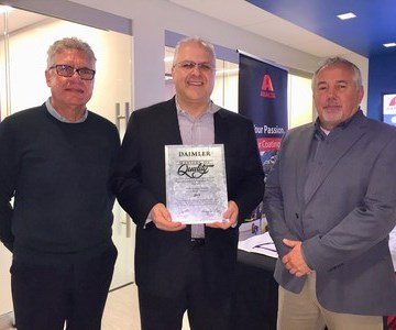 3 men holding award.