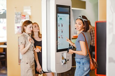A photo showing women ordering from a touchscreen menu at a quick service restaurant, an example of a product that MacDermid believes could benefit from Autotex AM