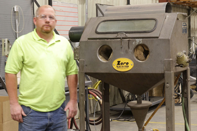 A photo of Eric Brukerhoff standing in front of the to-be-refurbished Zero BNP-270 blast cabinet