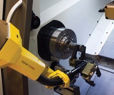 Robot arm reaches into machine for material handling