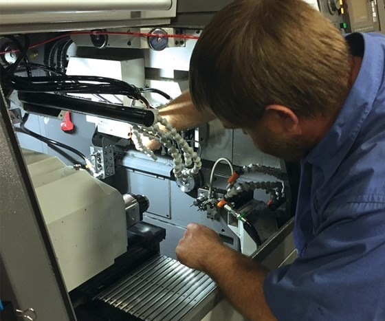 man working inside Swiss machine