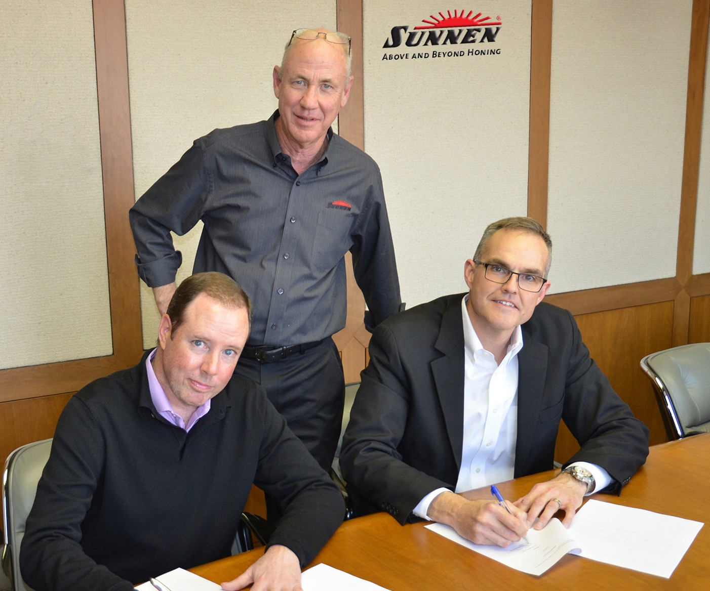 Executives signing papers for acquisition
