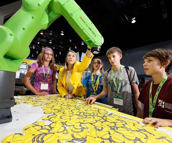 students standing around FANUC robot arm