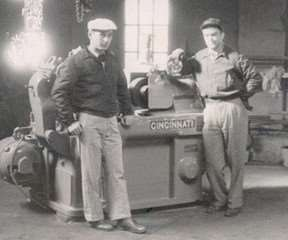 Old black and white photo of two men standing by old grinding machine