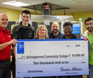 students holding large check representing grant award