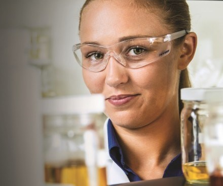 woman with safety glasses in a lab