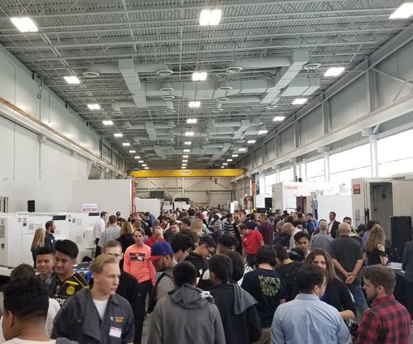 group of high school students gathered in hall featuring several machine tools