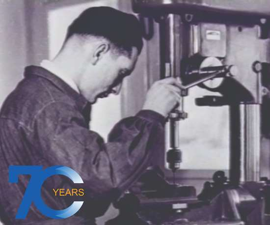 old black and white picture of man operating old machine