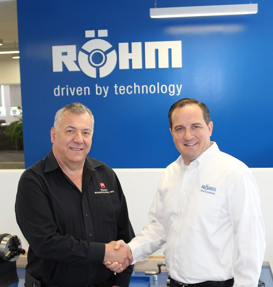 two men shaking hands in front of a Rõhm sign
