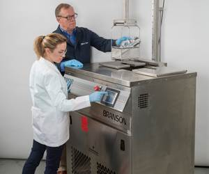 two people operating a vapor degreasing machine