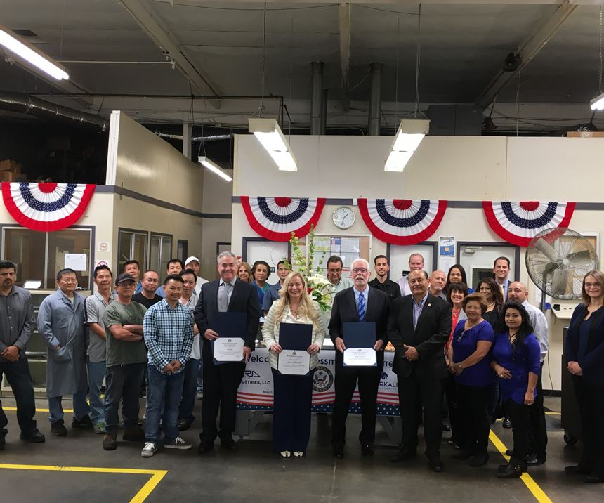 group of R.A. Industries' employees and Rep. Lou Correa displaying awards