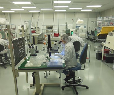 Employees assembling medical parts in a clean room