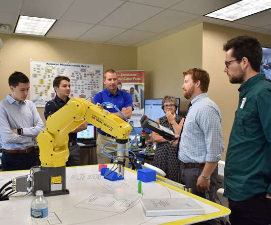 students standing around a robot arm during a demo