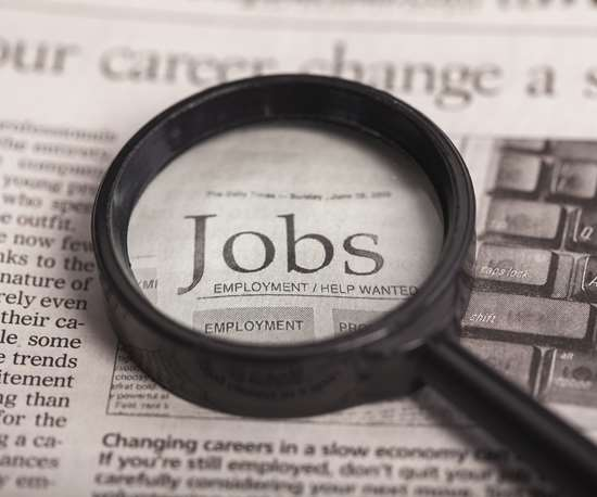 magnifying glass over JOBS in newspaper