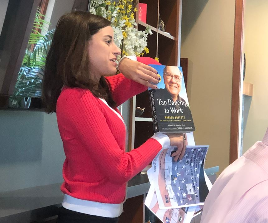 female intern holding up book authored by Warren Buffet