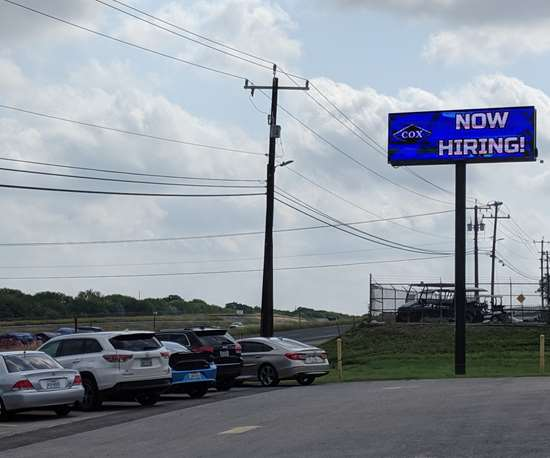 """Now Hiring"" billboard outside Cox Manufacturing"
