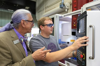 Dean Baker teaches a student how to use a machine control