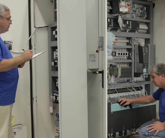 Siemens employees working on an electrical cabinet