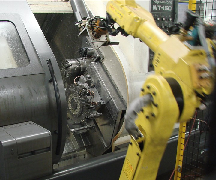 Robotic arm loading and unloading a lathe